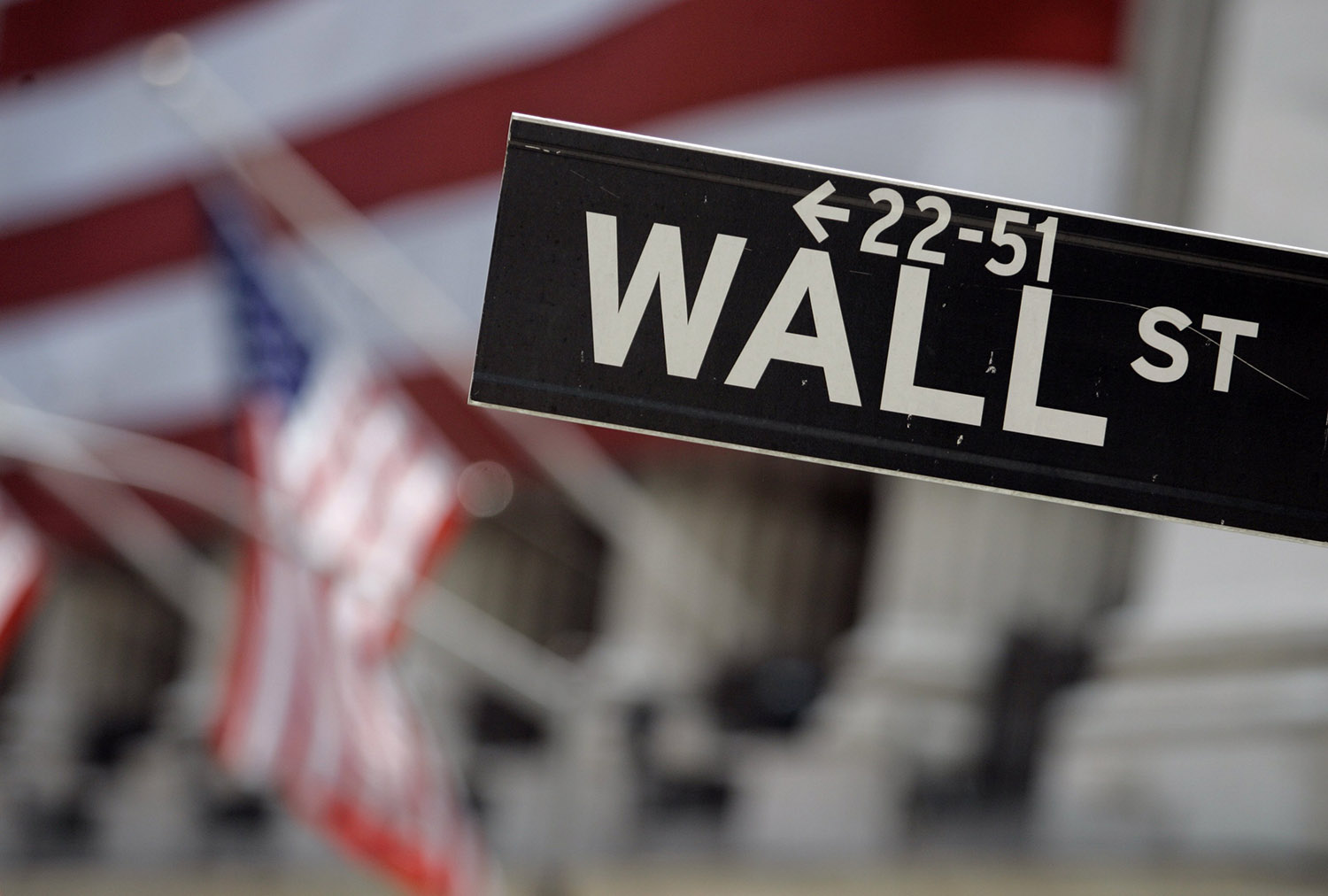 Wall Street sign is mounted near the flag-draped facade of the New York Stock Exchange